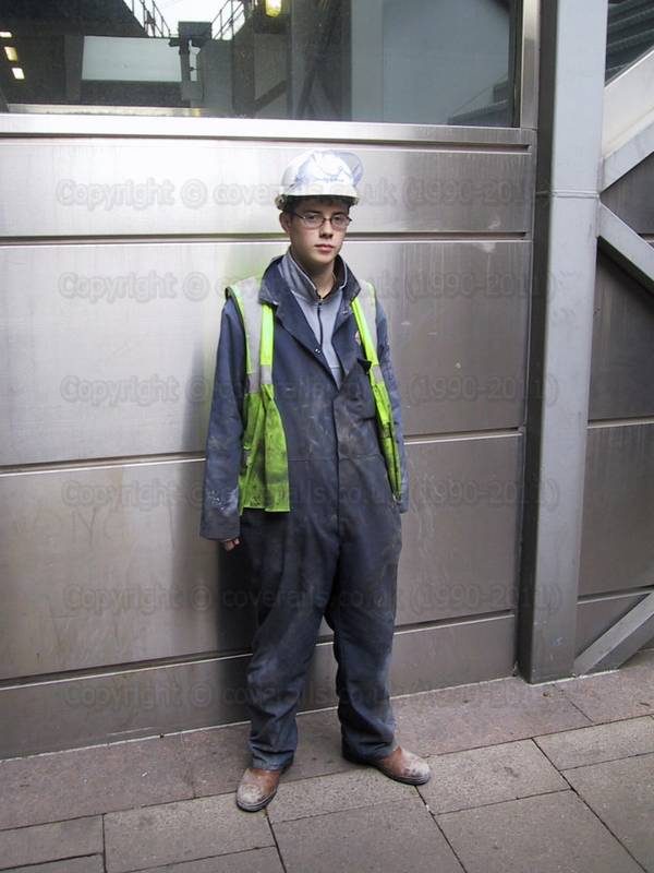 Young Apprentice at Canary Wharf wearing dirty blue coveralls, yellow hi-vis waistcoat and a white hardhat. Young Apprentice at Canary Wharf wearing dirty blue coveralls 3