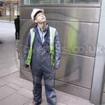 Young Apprentice at Canary Wharf wearing dirty blue coveralls, yellow hi-vis waistcoat and a white hardhat