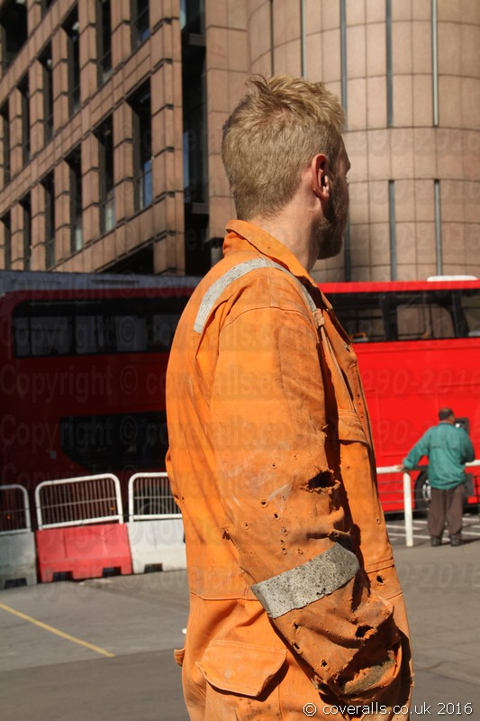 Blond Guy rail worker wearing an old worn orange hi-vis boiler suit. Blond Guy Wearing Old Worn Orange Boiler Suit 2