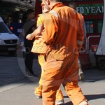 Blond Guy rail worker wearing an old worn orange hi-vis boiler suit