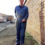 Young woodworker wearing blue overalls