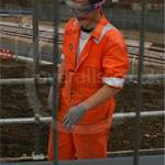 Boy wearing orange hi-vis wenaas coveralls white hardhat working on the DLR extension