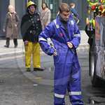 Boy wearing a very oversized baggy blue hi-vis boilersuit at the lord mayors show
