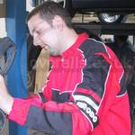 Car Mechanic fitting a new chrome exhaust system wearing a Ferodo overall
