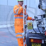 Driver pouring new concrete wearing Orange Hi-vis coverall