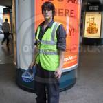 Young lad wearing blue coveralls and yellow hi-vis waistcoat at Canary Wharf