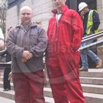Young construction workers wearing red overalls at Canary Wharf