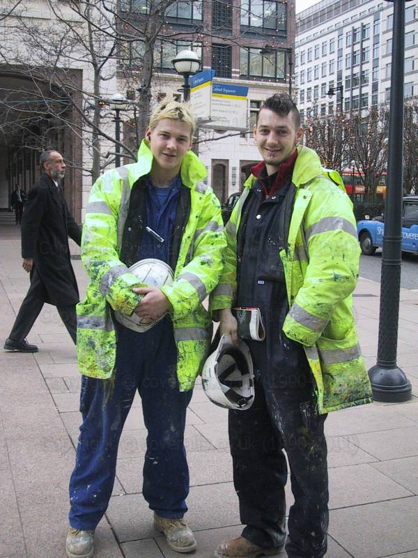 Painters working in Canary Wharf wearing overalls and yellow hi-vis coats splattered with blue paint 45