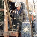 Craig drilling, wearing a brown muddy coverall