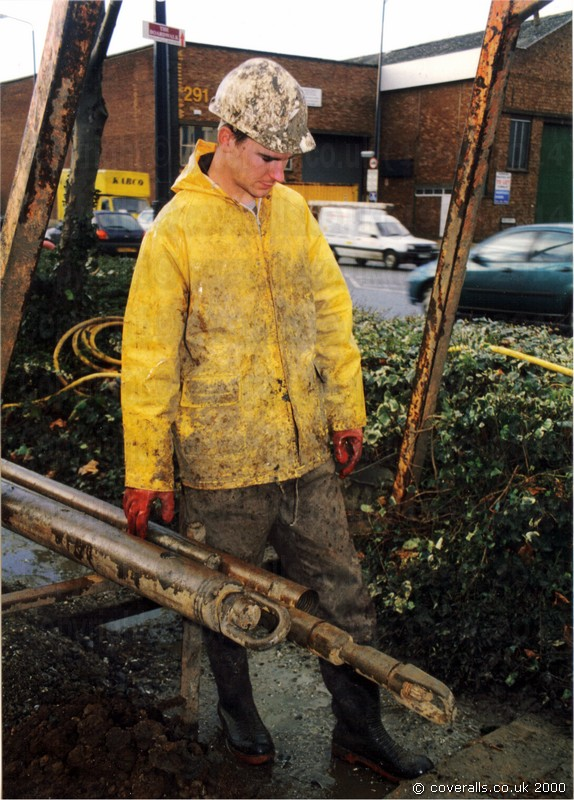 Craig drilling, wearing a brown muddy wet coverall and PVC rain jacket 2