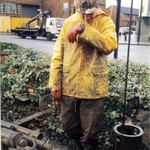 Craig drilling, wearing a brown muddy wet coverall and PVC rain jacket