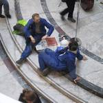 workmen at lunch in blue coveralls at Canary Wharf