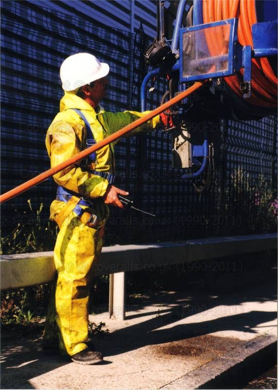 Drain sewage engineer in yellow pvc coveralls and fall arrest safety harness. Drain sewage engineer in yellow pvc coveralls 1