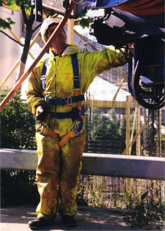 Picture of Drain sewage engineer in yellow pvc coveralls and fall arrest safety harness