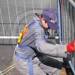 Drain service engineer wearing grey coveralls and safety harness