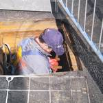 Drain service engineer wearing grey coveralls and safety harness entering manhole