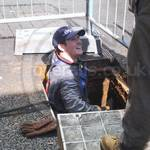 Drain service engineer wearing grey coveralls and safety harness emerging from manhole