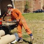 Paul doing some soil drilling, wearing orange coverall, hardhat and mud