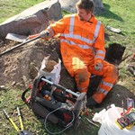 Electricity worker fixing cables wearing Orange ProGarm Hi-vis coveralls