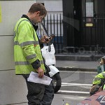 Electricity workmen repairing power cables in the street wearing black parachute type coveralls