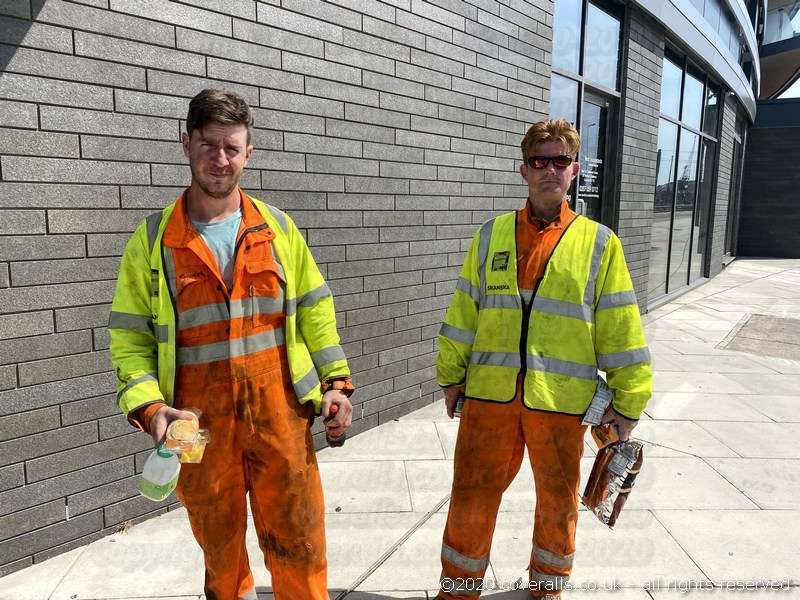 Workman wearing hi-vis Orange Boilersuits and yellow hi-vis waistcoats. Engineers Orange Boilersuits 1