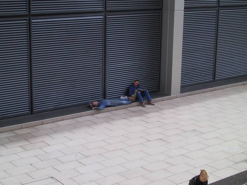 Guys lying down in Canary Wharf 2