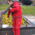 Guy putting on his red coverall being help by a mate wearing a grey coverall