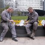 Guys eating lunch wearing grey coveralls in Canary Wharf