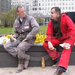 Two guys sitting one wearing a grey coverall, one wearing a red coverall