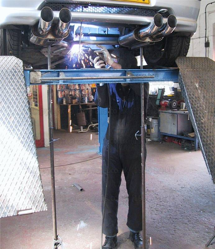 Garage Mechanic fitting a new car exhaust wearing a plain blue overall. Garage Mechanic 23