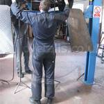 Garage Mechanic fitting a new car exhaust wearing a plain blue overall