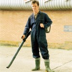 Gardener, wearing blue coveralls and using a leaf blower