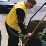 Gardener lad wearing blue boilersuit yellow hi-vis jacket doing a bit of weeding down by the river thames
