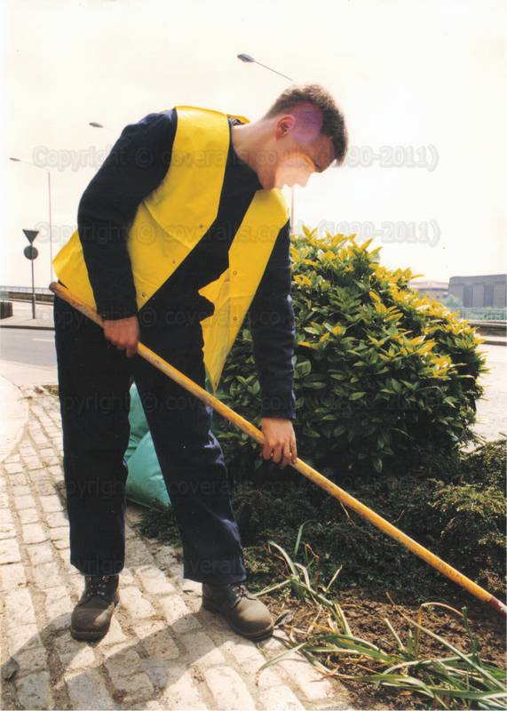Picture of Gardener lad wearing blue boilersuit yellow hi-vis jacket doing a bit of weeding down by the river thames