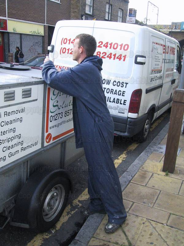 Graffiti removal operative wearing blue waterproof coverall 1