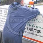 Graffiti removal operative wearing blue waterproof coverall