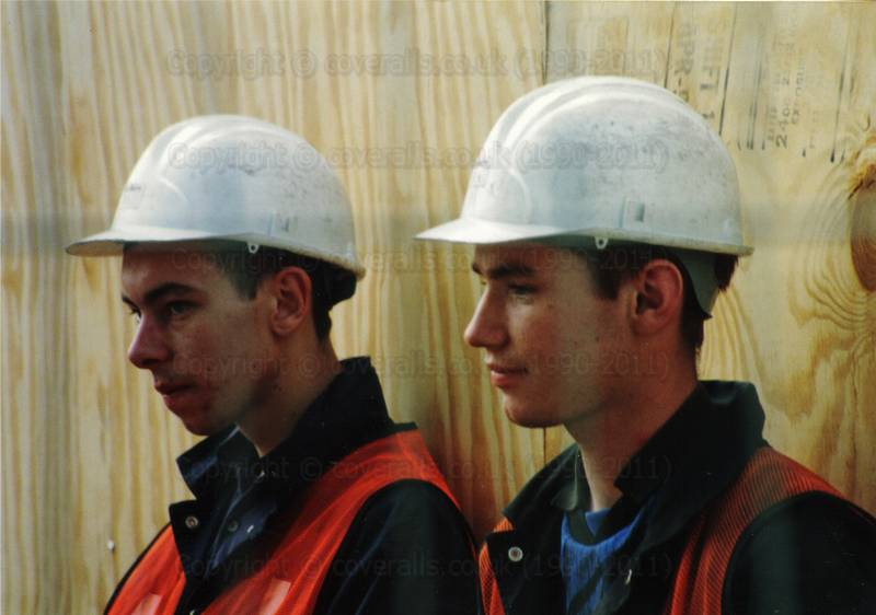 Young lads wearing blue coveralls and orange hi-vis waistcoats guarding the site works of the M11 link road in the last battle at Claremont Road 1