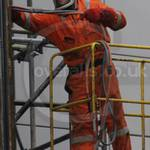 Welder using an Oxy-Propane cutting torch working wearing a pair of orange Hi-vis Nexus Zero Flame coveralls
