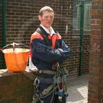Highrise building cleaner wearing blue/orange coveralls 1