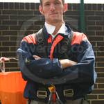 Highrise building cleaner wearing blue/orange coveralls