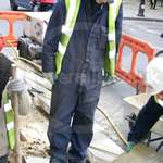 Utility worker James wearing navy blue coveralls digging up the pavement