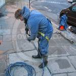 Young Lad Steam/Jet washing buildings wearing waterproof PVC Coverall