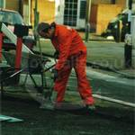 Road digger, wearing orange coveralls