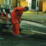 Guy digging road, wearing orange coveralls