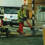 Guy digging road, wearing orange coveralls and a hi-vis fluorescent jacket