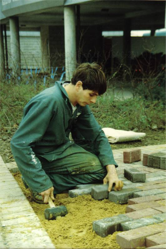 Picture of lad laying a brick path wearing a green boilersuit