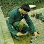 lad laying a brick path wearing a green boilersuit