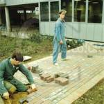two lads laying a brick path, one wearing a green boilersuit, the other a blue boilersuit