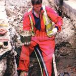 Electrician from LEB digging up the road in order to mend an underground electricity cable, wearing red coveralls and hi-vis fluorescent vest