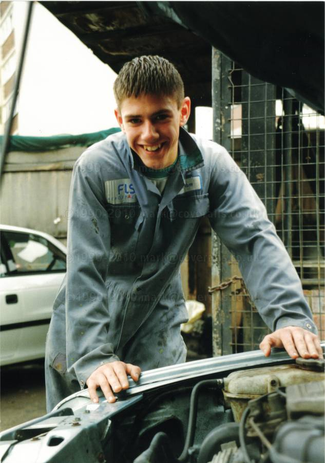 Young car mechanic in light blue overall 1